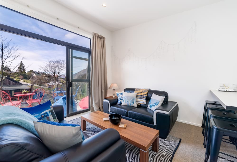 The spacious living area opens almost fully onto the balcony. Gaze at the everchanging view of the Remarkables, relax on a beanbag or dine in style in a fun cafe-style setting