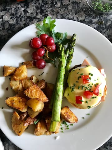 Eggs Benedict with herb roasted potatoes and locally grown asparagus.