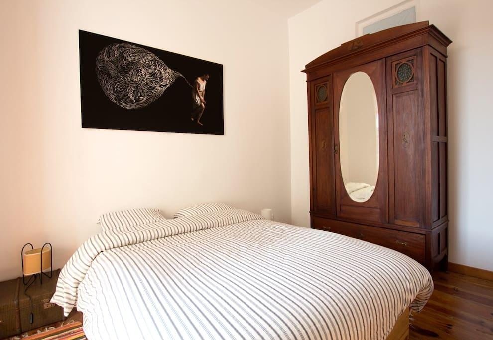 Os quartos deste apartamento foram cuidadosamente decorados, como se tratasse de habitação própria. A mobília enquadra-se com a idade do prédio. Este é um dos dois quartos com camas de casal.