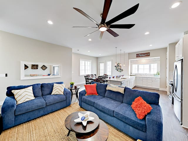 The living area is furnished with blue upholstered sofas and a striped accent chair for 6.