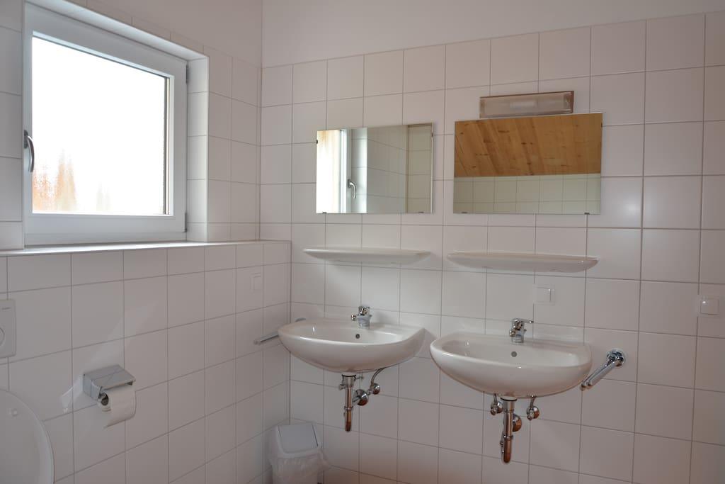 Badezimmer mit Waschbecken und Waschmaschine.