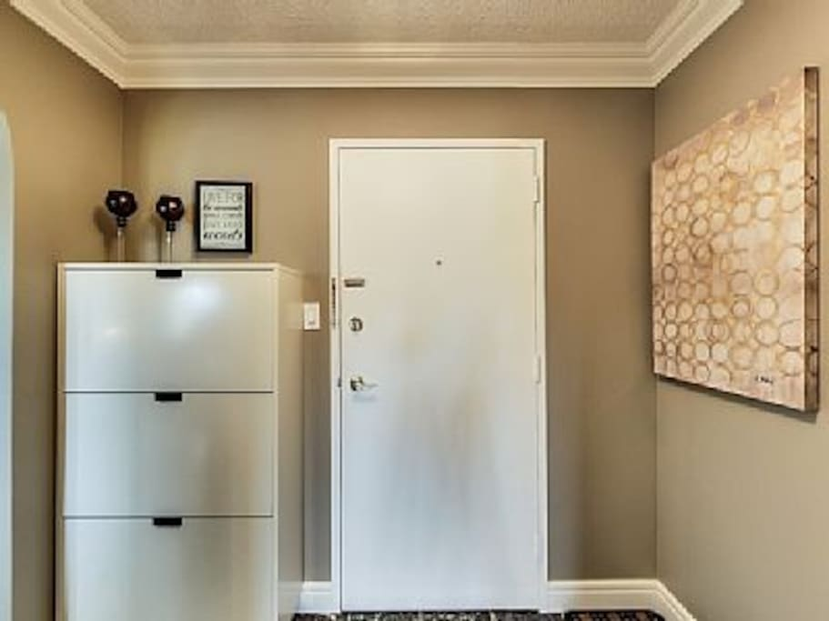 Separate foyer features shoe cabinet and marble floors.
