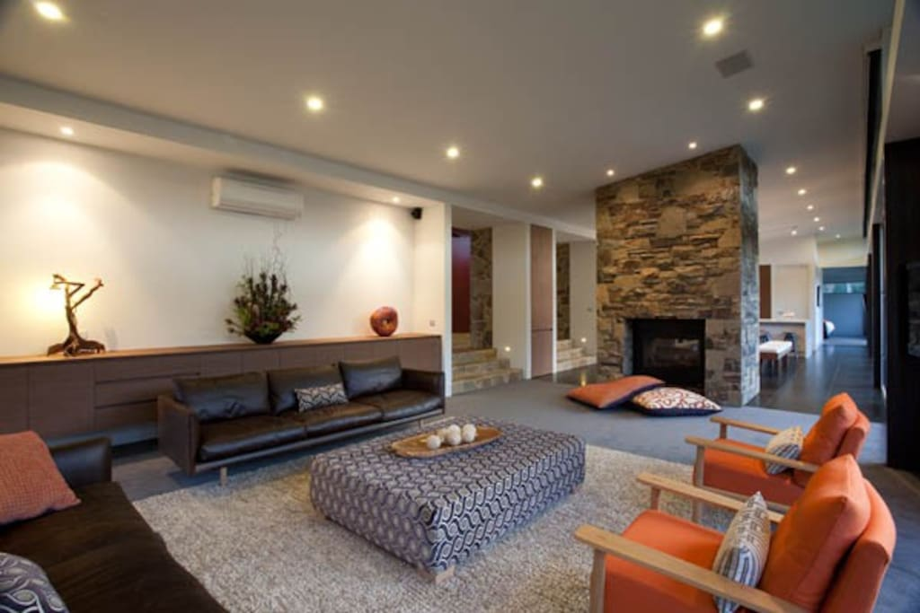 Relax in te lounge space with double sided hand laid stone fireplace