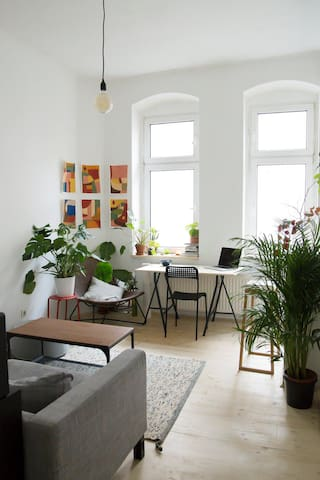 Our livingroom with sofa, coffe tables, plants, 2 big windows and a little studio side in the back
