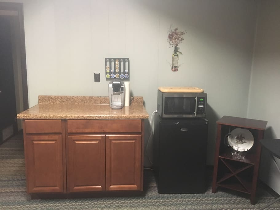 Kitchenette with Keurig, hot plate, Ninja blender, microwave, mini fridge and plates/silverware.