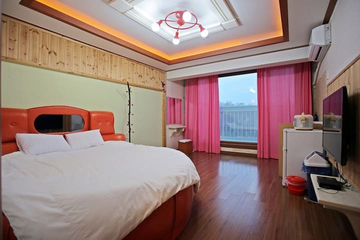 아늑한 원목거실과 침대가 있는 커플룸