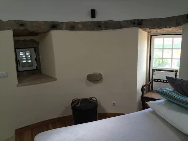 Schlafzimmer: Vom runden Raum im ersten Stock aus können die Gäste eine herrliche Aussicht genießen, dass der Norden uns den Strand von Porto Novo in Vimeiro präsentiert, und an seinen Seiten bietet uns dieselbe Aussicht eine schillernde ländliche Landschaft, die einer Postkarte würdig ist. Einfaches, aber charmantes Zimmer, das uns zu großartigen Momenten purer Entspannung und Entspannung inspiriert. Beim Öffnen der Fenster zeigen die Gemeinschaftsräume eine ruhige Natur, in der sich Blumen, Bäume, Pflanzen und ländliche Aktivitäten verbinden. Man kann die Vergangenheit noch einmal erleben, indem man den Mühlenmast beobachtet, der durch den oberen Raum des Raumes verläuft. Einige Merkmale der alten Mühle wurden erhalten, wie der obere Randstein und eine andere Art von dekorativem Stein.