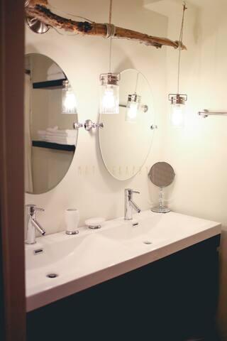 Bathroom vanity with custom light fixture.