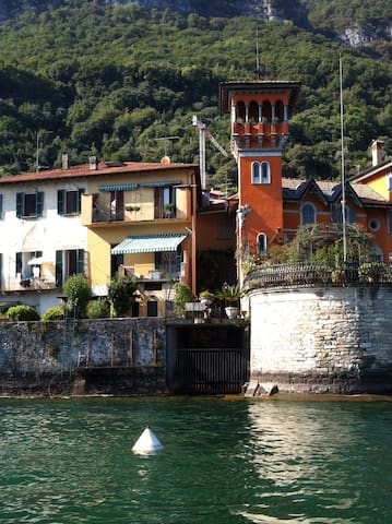 Exterior of apartment directly on the Lake with awning open.  Villa Camanni with the tower on the right