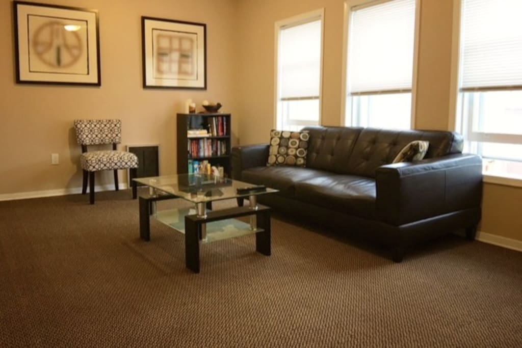 Large, bright living room with comfy leather couch