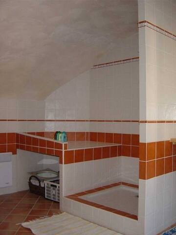 En plus de la grande douche, le coin buanderie comporte une machine à laver et un évier.