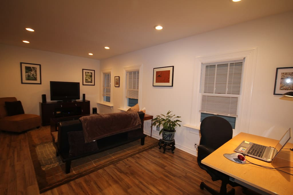 Living room with flat screen TV, surround sound, DVD player, workstation.