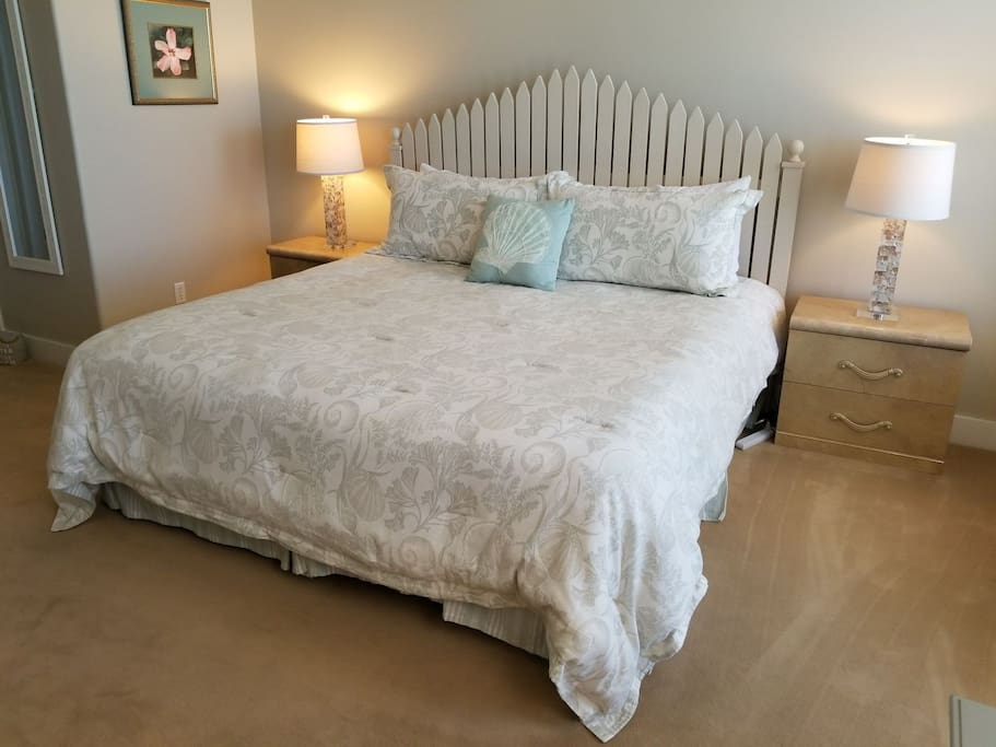 King bed with bedside tables and drawers and lamps always with working light bulbs and convenient power strips on both sides of the bed.