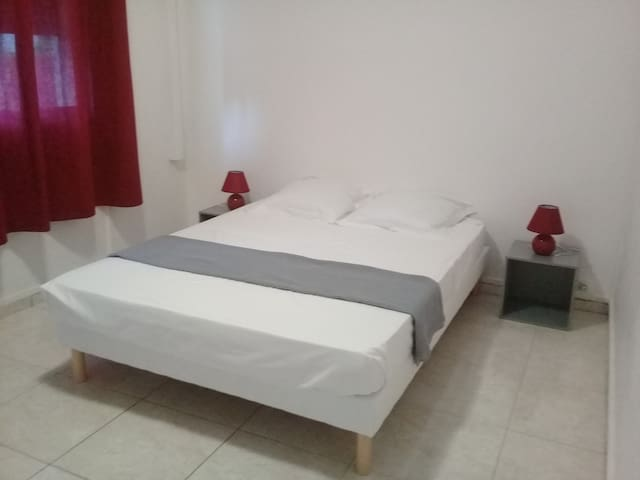 Chambre rouge et grise avec grand placard, 2 meubles avec lampes de chevet et 1 climatiseur individuel avec vue sur la montagne.