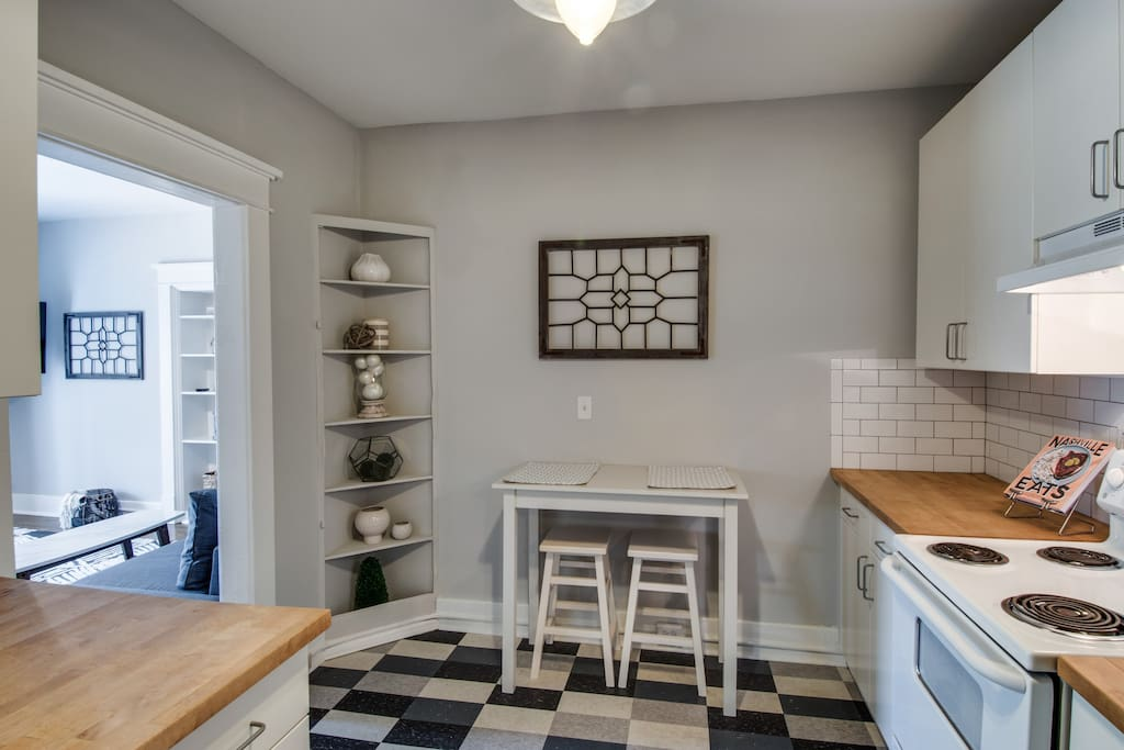 The kitchen features butcher block counters and mosaic tile floors.