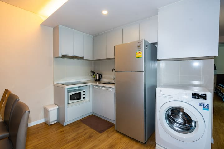 Washing machine, microwave, stove, and welcome water and soft drinks in the fridge