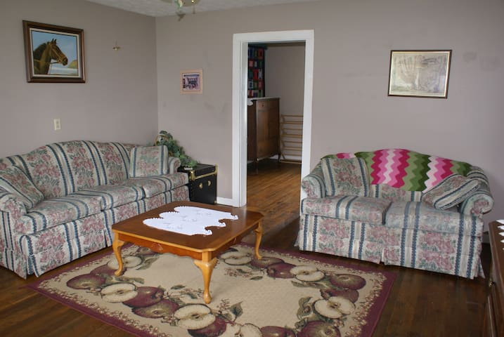 Living room with sofa, love seat, coffee table, entertainment unit with TV & VCR, movies, and games.