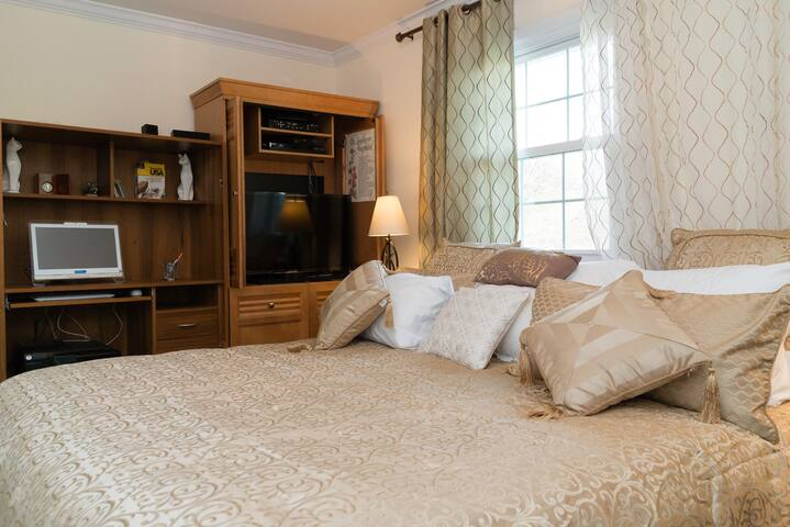Bedroom has flat-screen TV and large window behind bed.