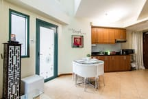 The glass door leads to the garden and direct access to the swimming pool and amenities.
