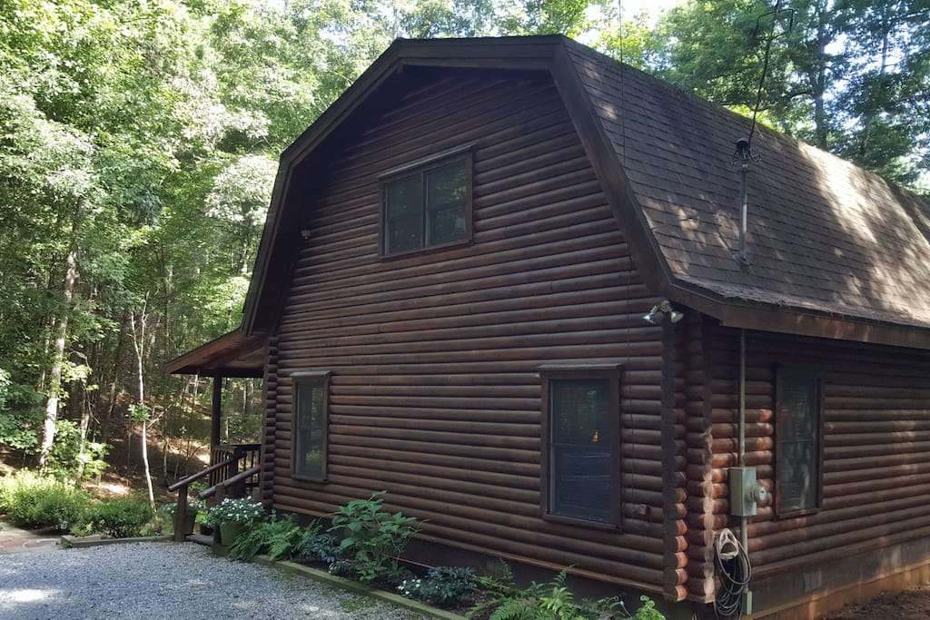 Entrance drive - front door and outdoor seating areas face wooded hillside on back of cabin.