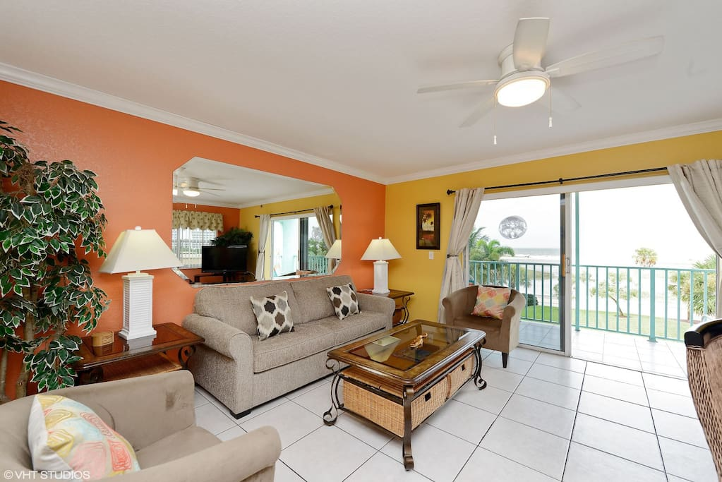 Large and inviting living area has a new sofa, large flat screen TV, and more impressive ocean views