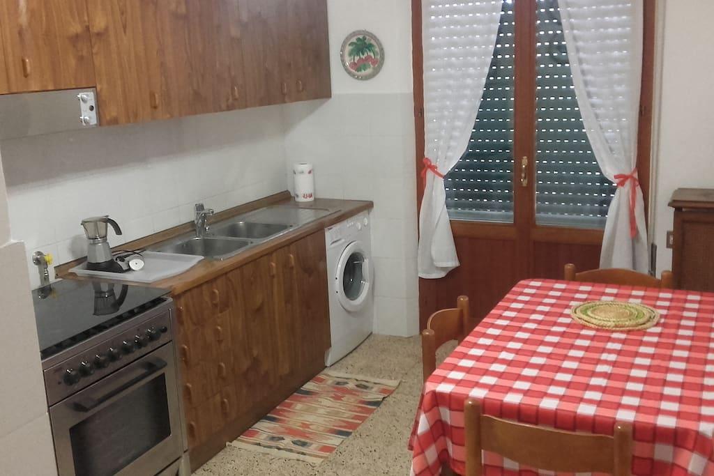 Cucina con lavatrice, forno, ecc.
