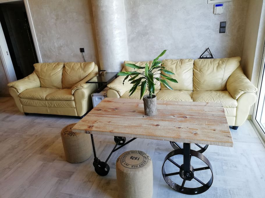 Living room with leather comfy couch and hand made table from wood and iron..