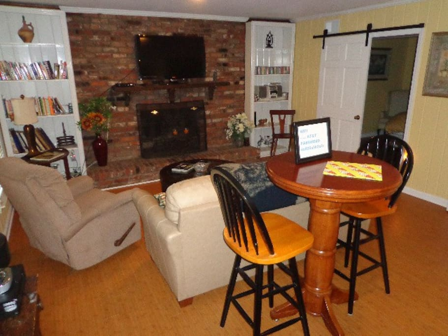 Living room with TV, pub table and sofa,recliner, CDs, WIFI,  and books