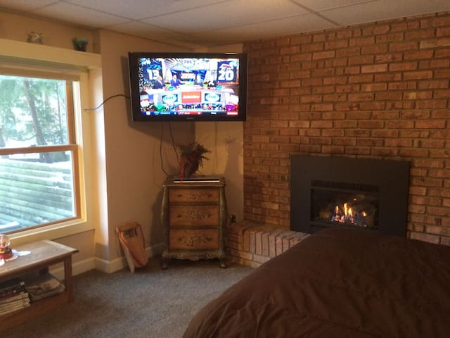 Large room with gas fireplace, large screen TV and view of wooded lot.