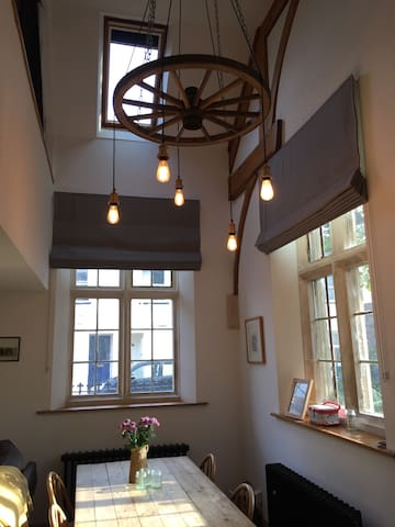 Double height dinning area, with Mullen windows and  wagon wheel light fitting