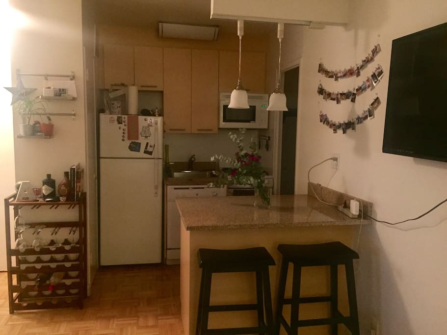 Kitchen with fridge, stove, dishwasher, microwave, bar style counter top table, and mini bar.