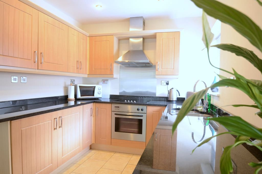Modern Kitchen with granite worktops, oven, hob, fridge, freezer, integrated washer/dryer and dishwasher.
