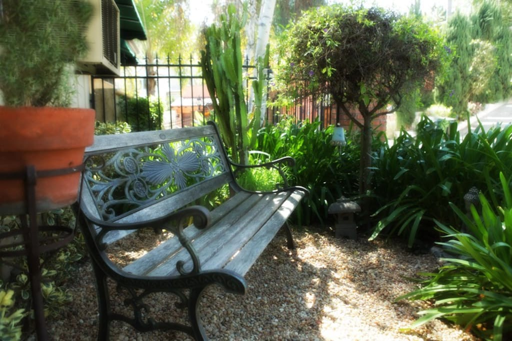 A mini zen garden with bench to sit and watch the neighbors pass with their dogs.