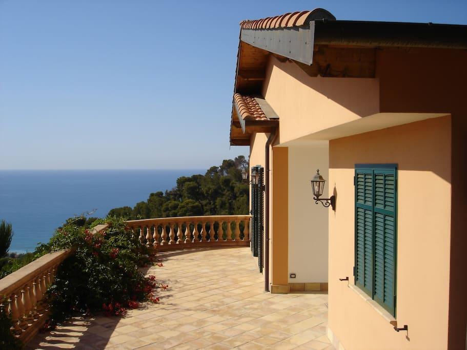 entrée principale de la maison avec une grande terrasse donnant sur une salle de fitness et une chambre
