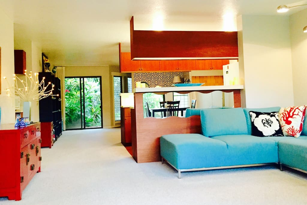 Spacious living-room with Natuzzi sectional, Balinese armoir and lush garden views