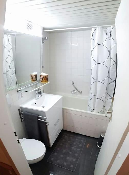 Großes helles Badezimmer mit Wanne. Föhn, Handtücher und Duschbad vorhanden.