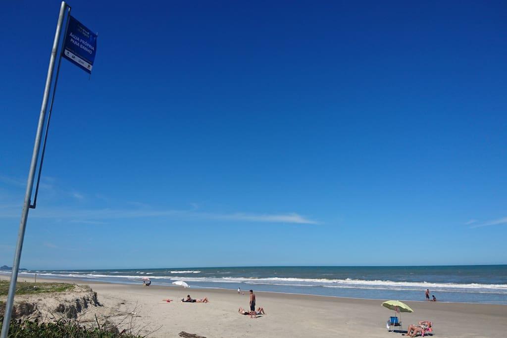 Vista da praia com bandeira azul de AGUA PRÓPRIA para banhos.