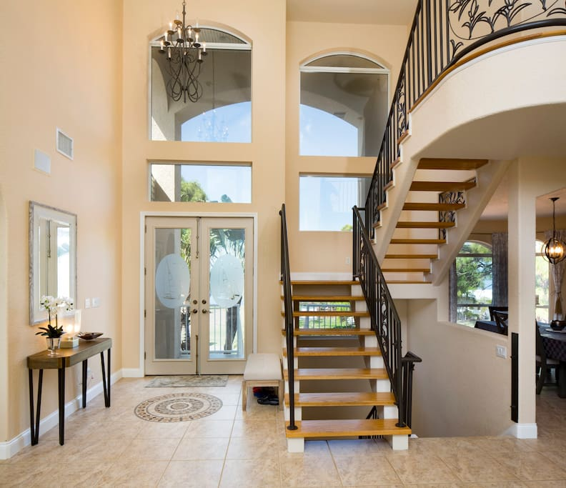 Grand Foyer with Double Doors, Soaring Windows, and Designer Wrought Iron Railing Floating Stairways