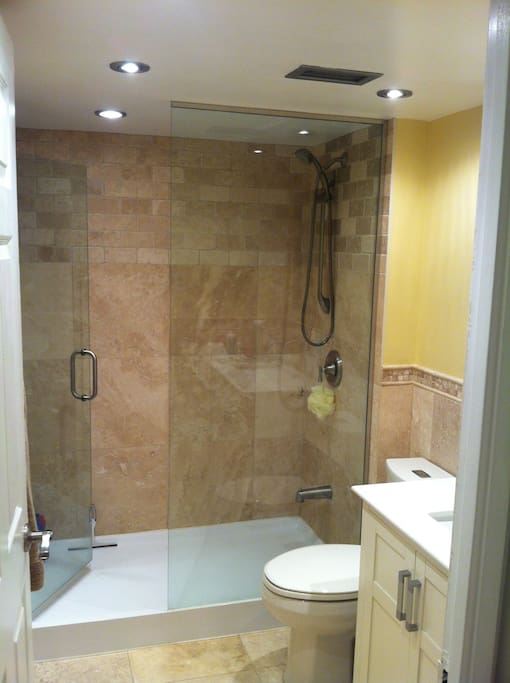 Recently renovated bathroom with travertine tile and custom glassed in shower.