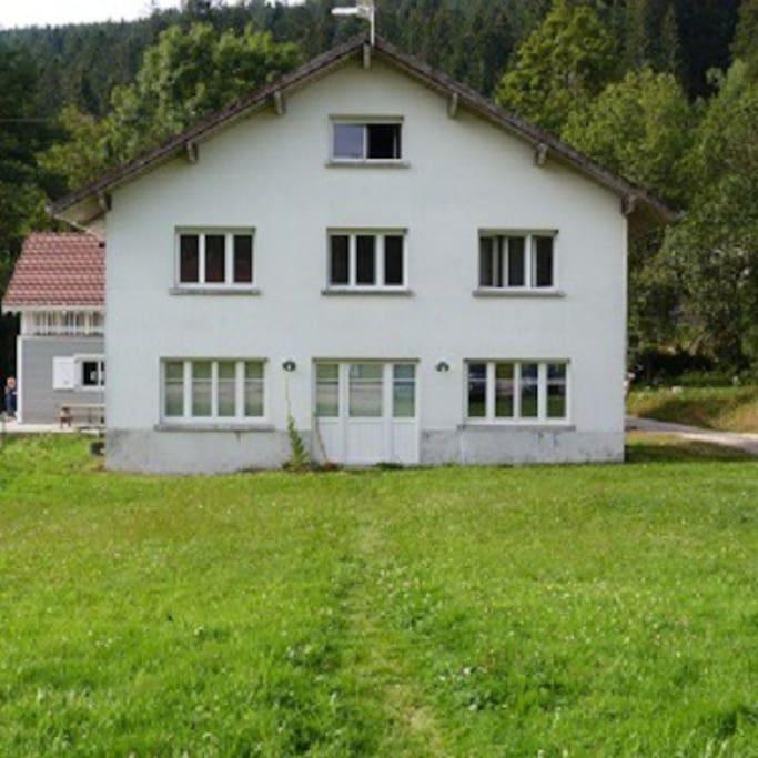 la maison avec un espace vert et une terrasse