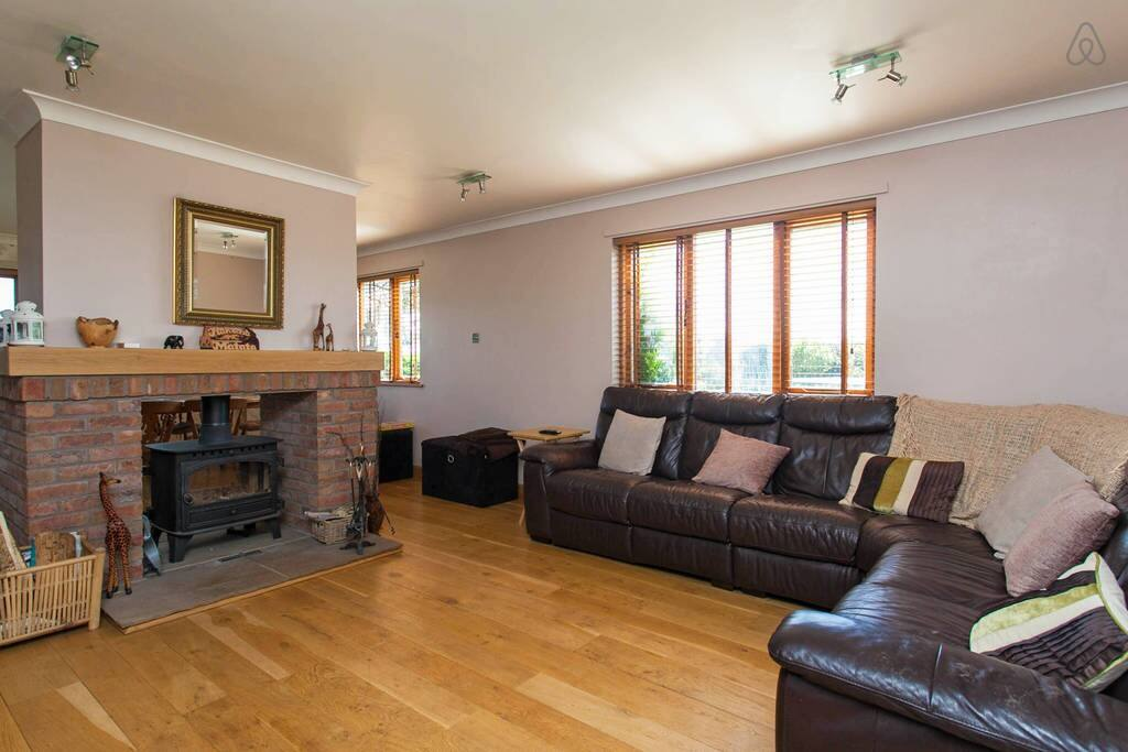 Living room with large reclining leather sofa, arm chairs and sky tv with sky on demand