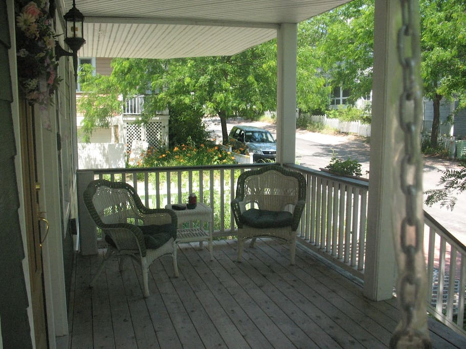 FRONT PORCH WITH SEATING AND A RATTAN SWING
