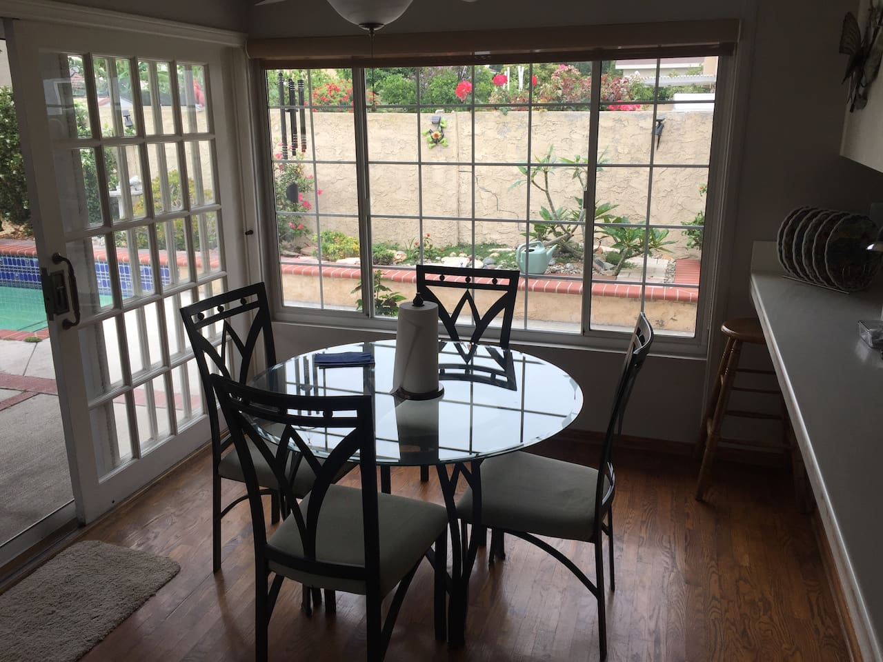 Eating area with view of pool and backyard. Ceiling fan is useful on warm days. Bar stool if you want to sit at the bar to watch someone cook your meal.