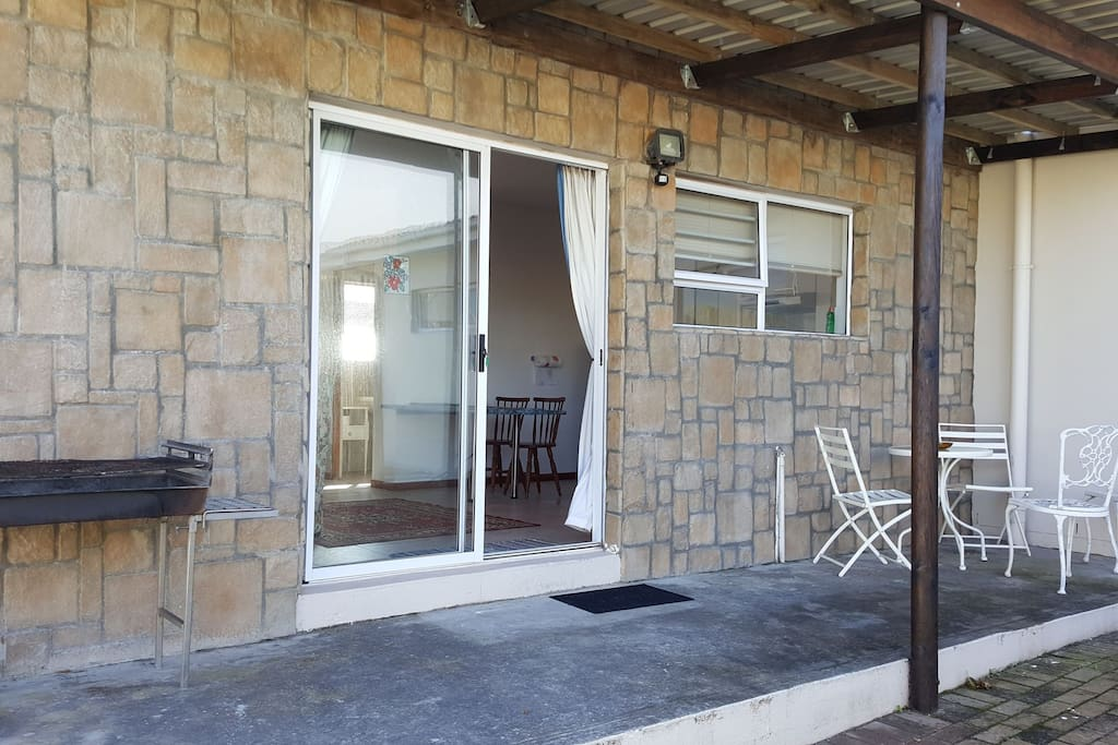Outside veranda with braai/barbeque facilities with garden furniture.