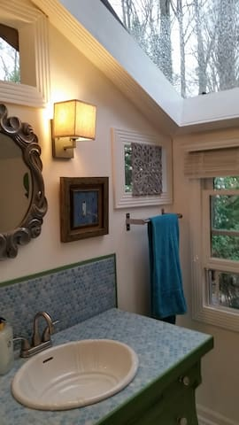 View of wall over antique bathroom vanity and wonderful skylight to the outdoors