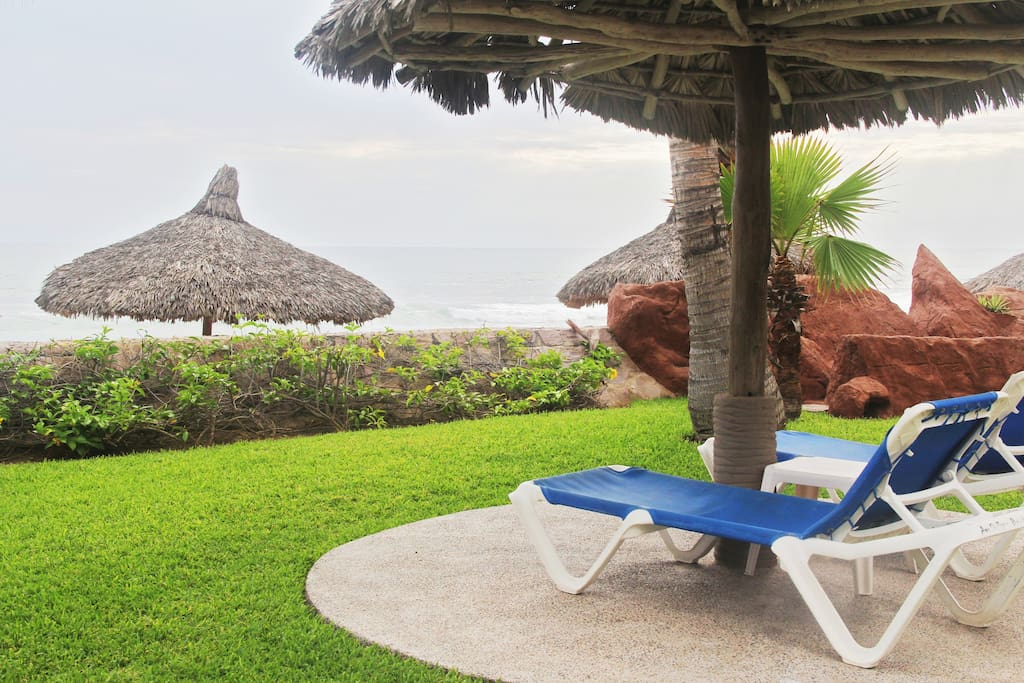 Garden area with palapas and lounge chairs.