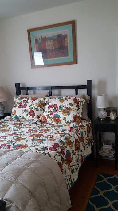 End tables and lamps on either sides of the queen bed.