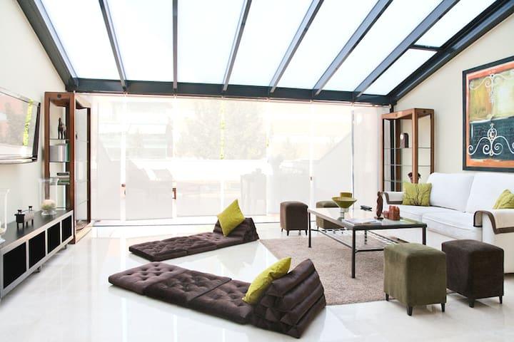 Salón con acceso a terraza por puertas plegables que dejan todo el espacio abierto.