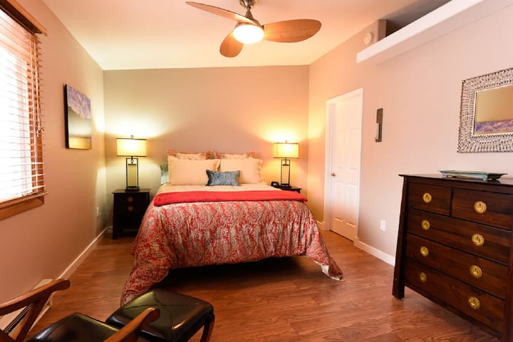 Bedroom with luxury linens, leather chair, walk-in closet and ceiling fan.