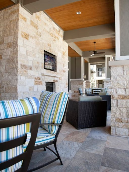 Poolside lounge with outdoor television and fireplace for use during the cool months